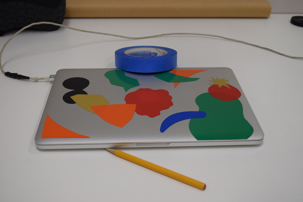 Image of silver laptop with colored stickers on it, sitting on a white table, with a yellow pencil and blue roll of tape. The whole image has no discernible color cast to it and the whites appear white.