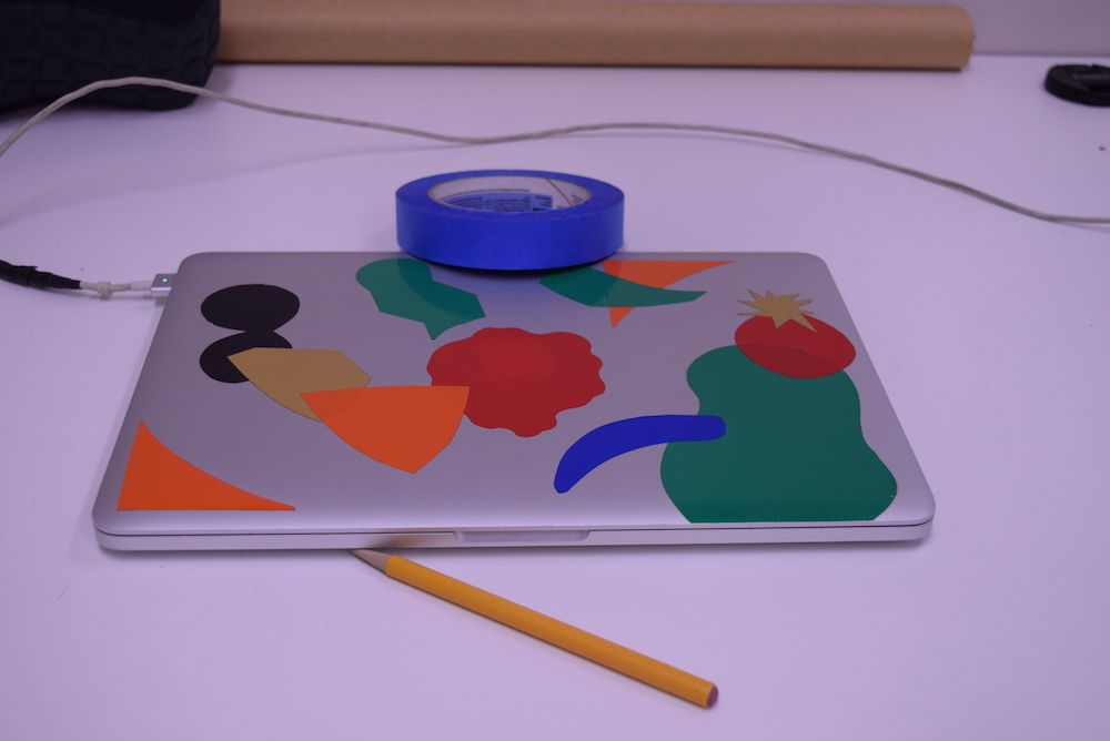 Image of silver laptop with colored stickers on it, sitting on a white table, with a yellow pencil and blue roll of tape. The whole image has a purple cast to it.