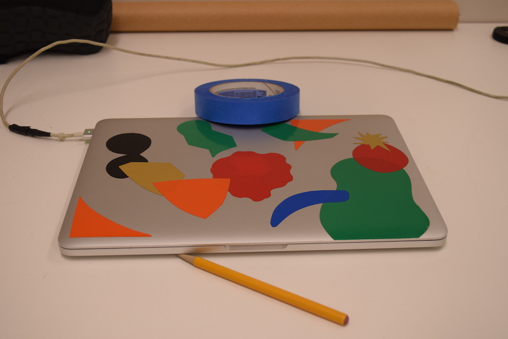 Image of silver laptop with colored stickers on it, sitting on a white table, with a yellow pencil and blue roll of tape. The whole image has a weak pink cast to it.