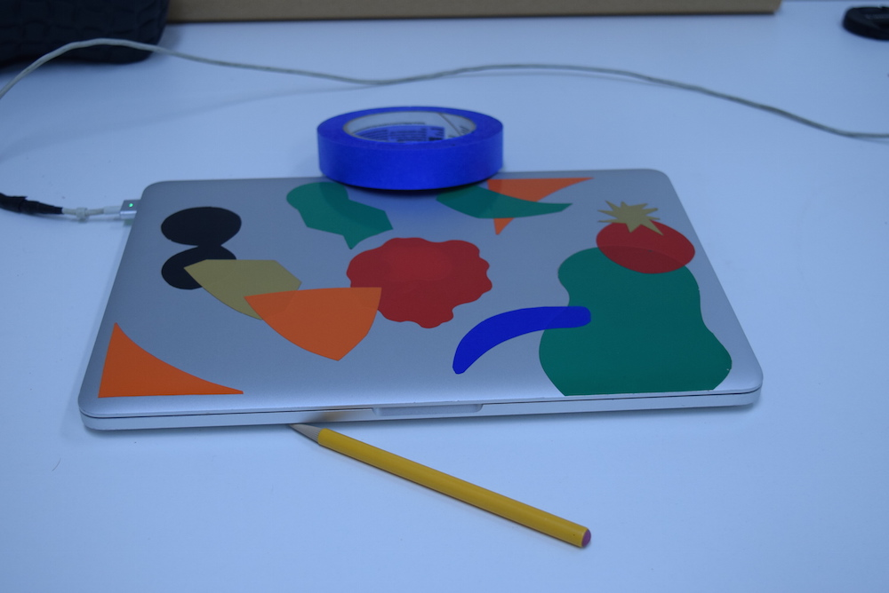 Image of silver laptop with colored stickers on it, sitting on a white table, with a yellow pencil and blue roll of tape. The whole image has a distinctly blue cast to it.
