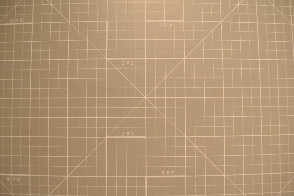 "Image of orthogonal grid pattern showing noticeable ""fisheye"" effect: the center of the image has no distortion, but moving towards the edges the grid lines are bent out as if the image were wrapped around a sphere."